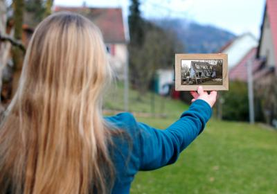 Frau hält einen Bilderrahmen mit einem Foto von einem Haus vor eine Baulücke